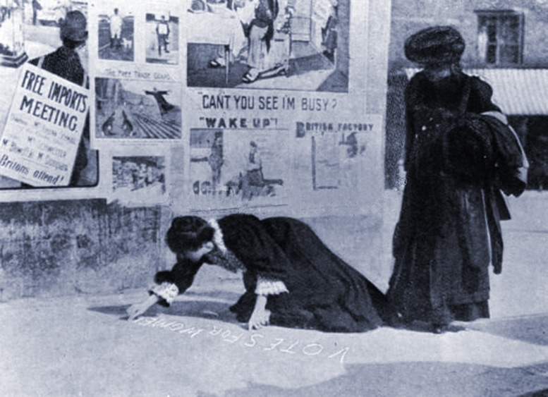 Writing on the pavement at Hexham, the by-election policy of the Suffragettes. Date 1907